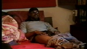 Muscled gangster jerks his big ebony cock on the bed