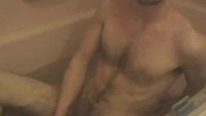 Real amateur guy lays in tub and jerks off his cock in the bathtub