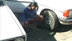 crazy girl pissing behind a car